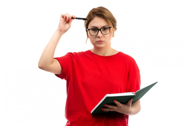 A front view young female student in red t-shirt holding copybook writing down notes thinking on the white Free Photo