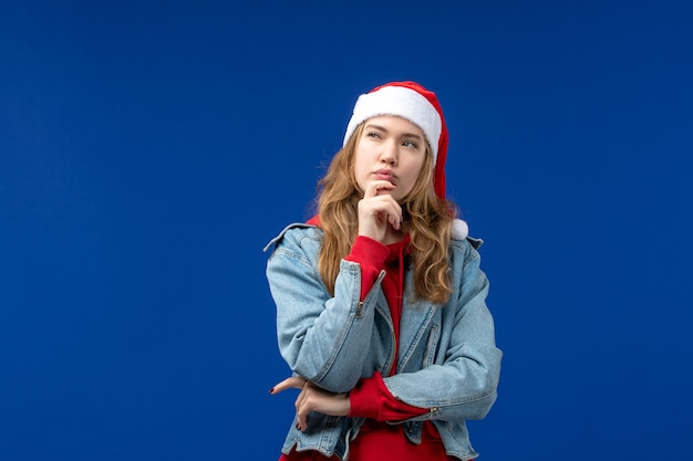 Vista frontale giovane femmina pensando su sfondo blu colore emozione vacanze di natale Foto Gratuite