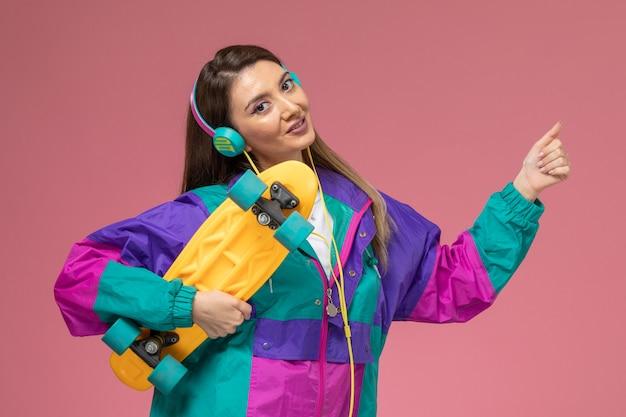 Vista frontale giovane femmina in camicia bianca cappotto colorato azienda skateboard Foto Gratuite