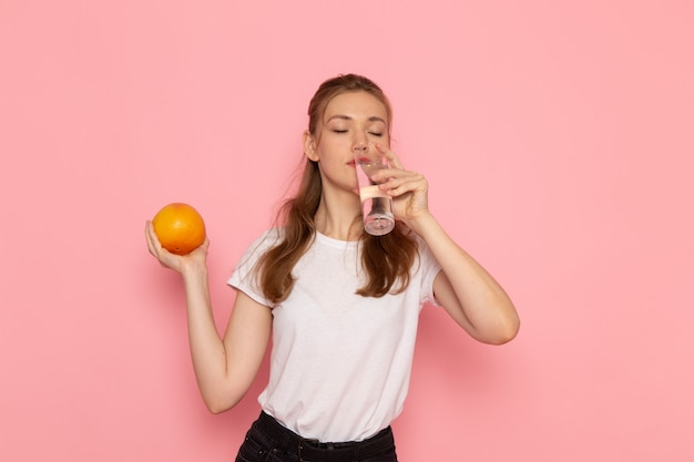 Vista frontale di giovane donna in maglietta bianca che tiene pompelmo fresco e bicchiere di acqua potabile sulla parete rosa Foto Gratuite