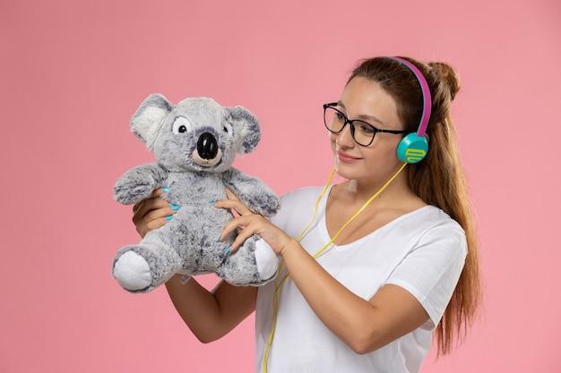 Giovane femmina di vista frontale in maglietta bianca che ascolta la musica tramite auricolari e che tiene il giocattolo sveglio sui precedenti rosa Foto Gratuite