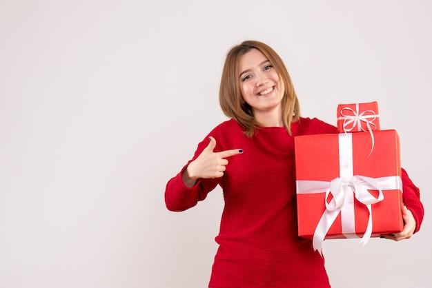 Вид спереди молодая женщина с рождественскими подарками Бесплатные Фотографии