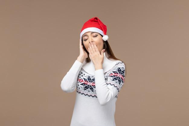 Giovane femmina di vista frontale che sbadiglia nel berretto rosso su sfondo marrone emozione natale capodanno Foto Gratuite