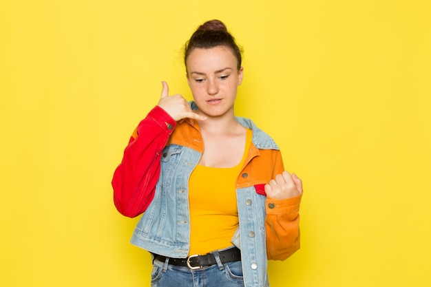 A front view young female in yellow shirt colorful jacket and blue jeans posing Free Photo