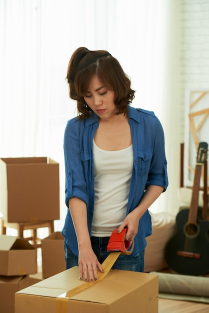 Front view of young girl packing the box with adhesive tape Free Photo