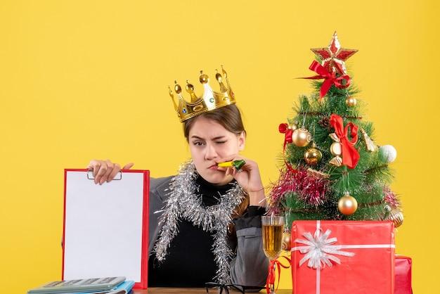 Вид спереди молодая девушка с короной, сидящая за столом, держащая документ, рождественскую елку и подарочный коктейль Бесплатные Фотографии
