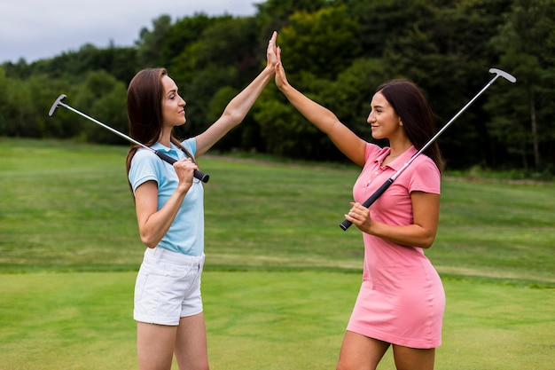 Front view of young golfers high fiving Free Photo