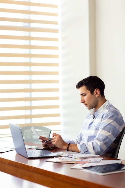 A front view young handsome man in striped shirt working inside conference hall using his silver laptop looking through documents writing down during daytime work activity building Free Photo