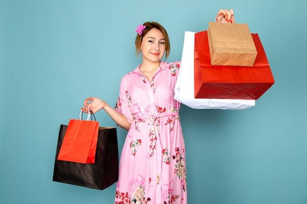 Una giovane signora di vista frontale in vestito dentellare progettato fiore che tiene i pacchetti della spesa e sorridere sull'azzurro Foto Gratuite