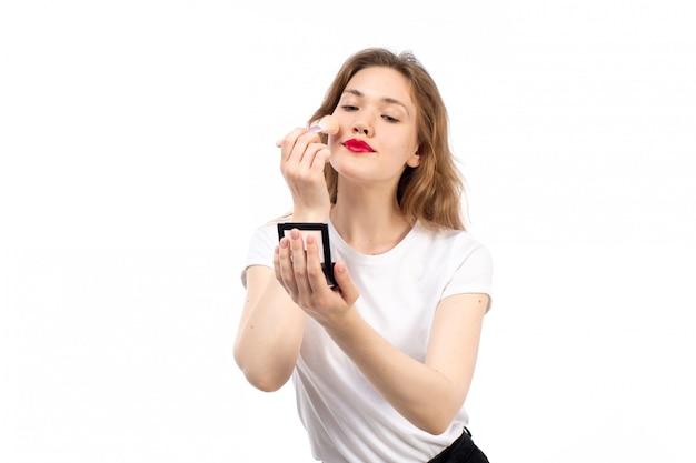 Una giovane signora di vista frontale in camicia bianca e pantaloni neri che fanno trucco sul bianco Foto Gratuite