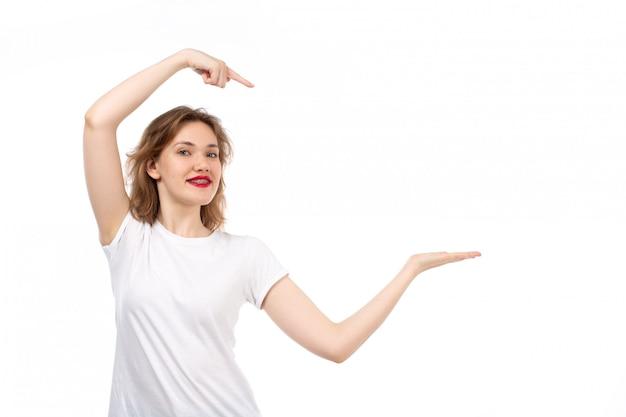 Una giovane signora di vista frontale in maglietta bianca che posa sorridere felice sul bianco Foto Gratuite