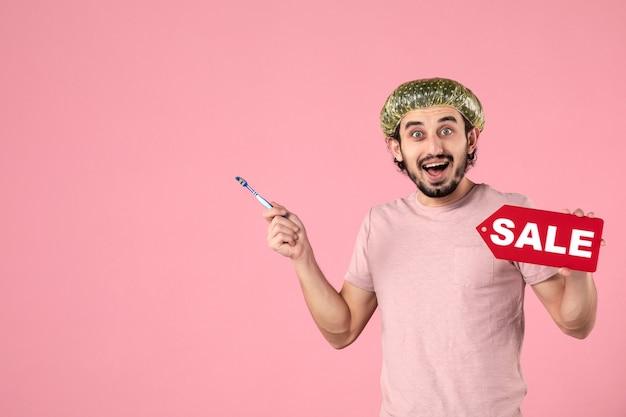 Vista frontale giovane maschio che pulisce i suoi denti e che tiene la targhetta di vendita su sfondo rosa Foto Gratuite
