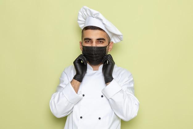Вид спереди молодой мужчина-повар в белом костюме повара в маске и перчатках на зеленом Бесплатные Фотографии