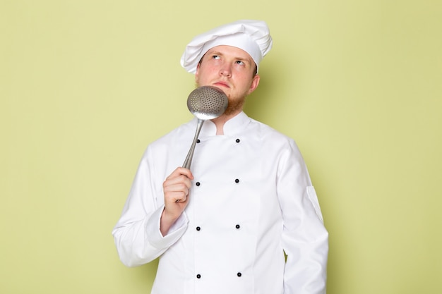 A front view young male cook in white cook suit white head cap holding big silver spoon thinking Free Photo