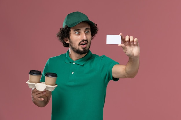 Front view young male courier in green uniform and cape holding delivery coffee cups and card on the pink background service job uniform delivery worker male Free Photo