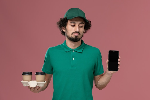Front view young male courier in green uniform and cape holding delivery coffee cups and phone on the light pink background service job uniform delivery Free Photo