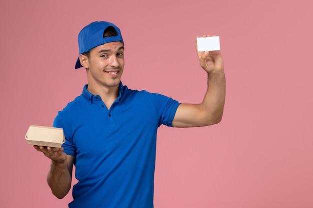 Вид спереди молодой курьер-мужчина в синей форменной накидке с небольшим пакетом еды для доставки и белой карточкой на светло-розовой стене Бесплатные Фотографии