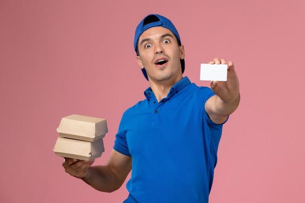 Вид спереди молодой курьер-мужчина в синей форменной накидке с небольшими пакетами еды для доставки с карточкой на светло-розовой стене Бесплатные Фотографии