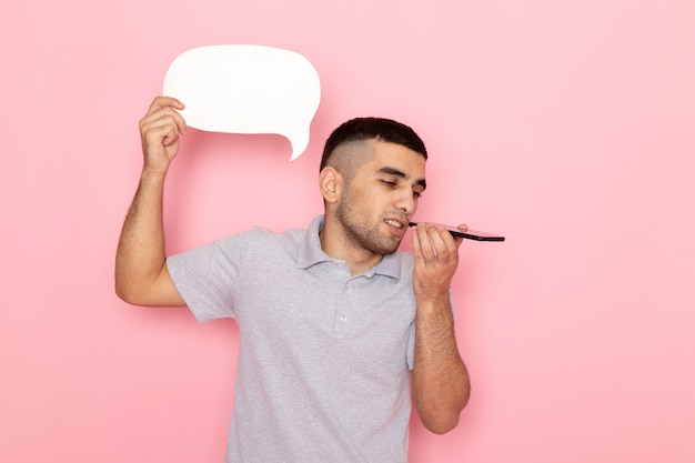 Front view young male in grey shirt holding white sign and talking on phone on pink Free Photo