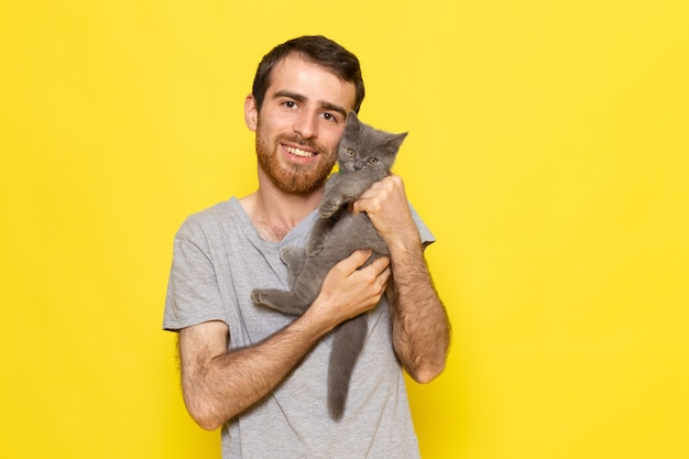 Un giovane maschio di vista frontale in maglietta grigia che tiene il gattino grigio sveglio sul modello di colore di emozione di espressione dell'uomo della parete gialla Foto Gratuite
