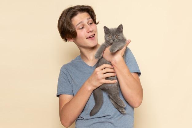 Un giovane maschio di vista frontale in maglietta grigia che tiene gattino grigio sveglio Foto Gratuite