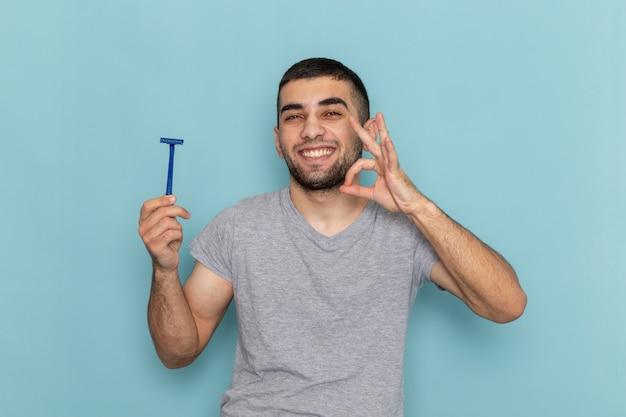 Giovane maschio di vista frontale in maglietta grigia che tiene il rasoio e che sorride sul colore maschio della schiuma dei capelli della barba dello scrittorio blu Foto Gratuite