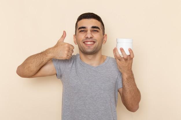 Giovane maschio di vista frontale in maglietta grigia che tiene la latta bianca con il sorriso sul beige Foto Gratuite