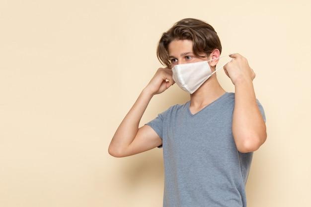 Un giovane maschio di vista frontale in maglietta grigia che porta una maschera Foto Gratuite