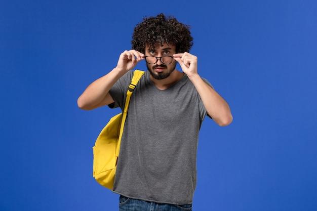Vista frontale del giovane maschio in maglietta grigia che porta zaino giallo sulla parete blu Foto Gratuite