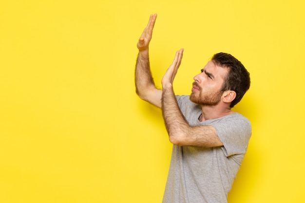 A front view young male in grey t-shirt with afraid expression on the yellow wall man expression emotion color model Free Photo