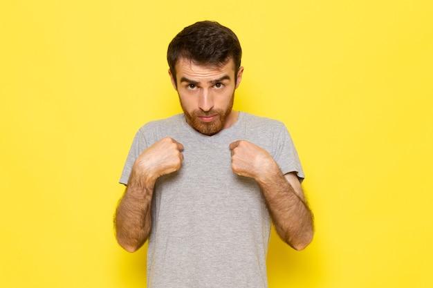 Un giovane maschio di vista frontale in maglietta grigia con l'espressione confusa sul colore giallo di emozione di espressione dell'uomo della parete Foto Gratuite