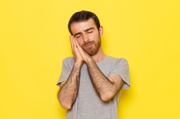 Un giovane maschio di vista frontale in maglietta grigia con posa addormentata sul modello di colore dell'uomo della parete gialla Foto Gratuite