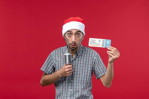 Front view young male holding plane ticket and mic on red background Free Photo