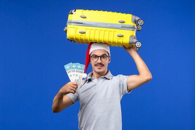 파란색 배경 비행 휴가 비행기에 티켓과 무거운 가방을 들고 전면보기 젊은 남성 무료 사진