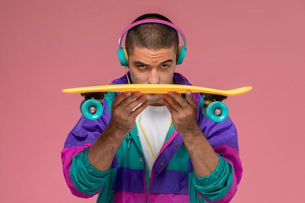 Вид спереди молодой самец в красочном пальто, слушающий музыку на розовом столе Бесплатные Фотографии