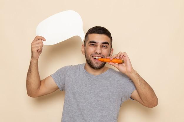 Вид спереди молодой самец в серой футболке с белым знаком и ест морковь на бежевом Бесплатные Фотографии