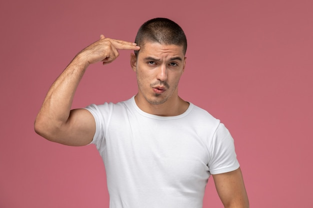 ピンクの背景に彼の寺院に触れるポーズ白いtシャツで正面の若い男性 無料写真