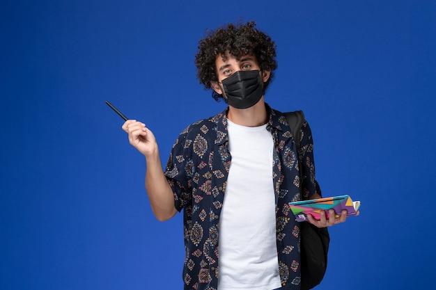 Giovane studente maschio di vista frontale che porta maschera nera con il quaderno e la penna della tenuta dello zaino sui precedenti blu. Foto Gratuite