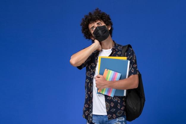 ファイルと青い机の上に首の痛みを持っているコピーブックを保持しているバックパックと黒いマスクを身に着けている正面図の若い男子生徒。 無料写真