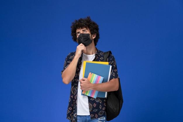 青い机の上でファイルとコピーブック思考を保持しているバックパックと黒いマスクを身に着けている正面図の若い男子生徒。 無料写真