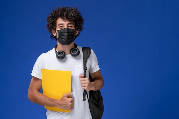 Giovane studente maschio di vista frontale in maglietta bianca che porta maschera nera e che tiene file gialli su sfondo azzurro. Foto Gratuite