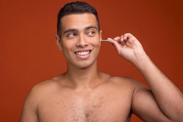 Giovane maschio di vista frontale usando i bastoncini dell'orecchio Foto Gratuite