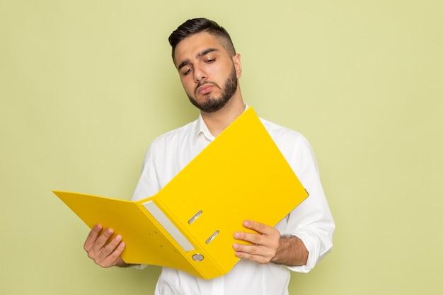 Un giovane maschio di vista frontale in camicia bianca che tiene gli archivi gialli e lo legge Foto Gratuite
