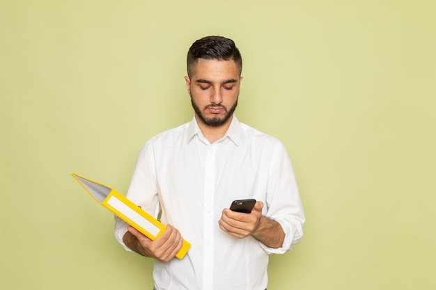 Un giovane maschio di vista frontale in camicia bianca che tiene archivi gialli e usando il suo telefono Foto Gratuite