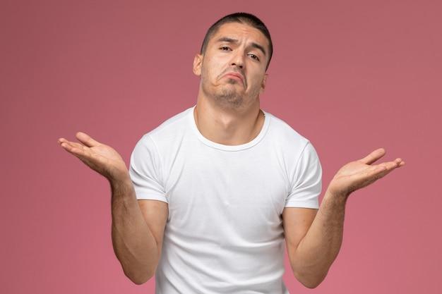 Giovane maschio di vista frontale in camicia bianca che posa con l'espressione confusa sui precedenti rosa Foto Gratuite
