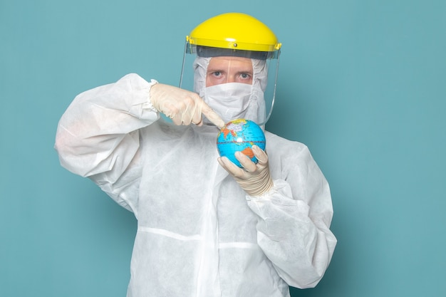 A front view young male in white special suit and yellow special helmet holding globe on the blue wall man suit danger special equipment color Free Photo