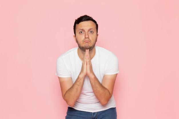 Un giovane maschio di vista frontale in maglietta bianca e blue jeans che posano e che implorano sulla posa rosa di emozione di colore dell'uomo dello scrittorio Foto Gratuite
