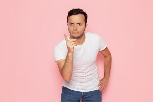 Un giovane maschio di vista frontale in maglietta bianca e blue jeans che minacciano sulla posa rosa di emozione di colore dell'uomo dello scrittorio Foto Gratuite