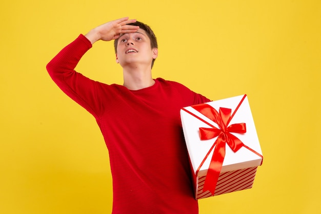 Giovane maschio di vista frontale con il grande presente di natale che esamina la distanza su fondo giallo Foto Gratuite