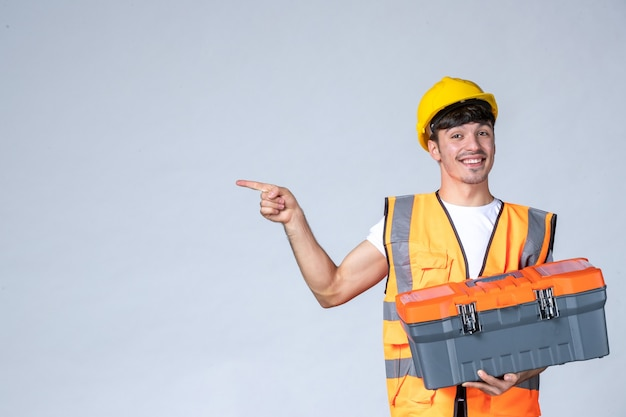Front view young male worker holding heavy tool case on white background Free Photo